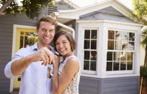 A couple outside their new house holding the keys.