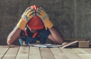 A builder looking sad due to construction running into many problems, of which a building code violation is just one.